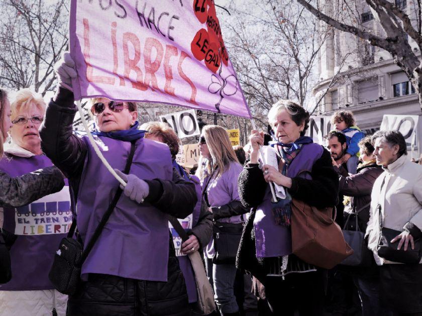 """Mujeres de la Marea Violeta sostienen una pancarta: """"decidir nos hace libres"""". El Tren de la Libertad. Manifestación contra la Ley Gallardón del Partido Popular. Fotografía de Luis F. Roncero."""