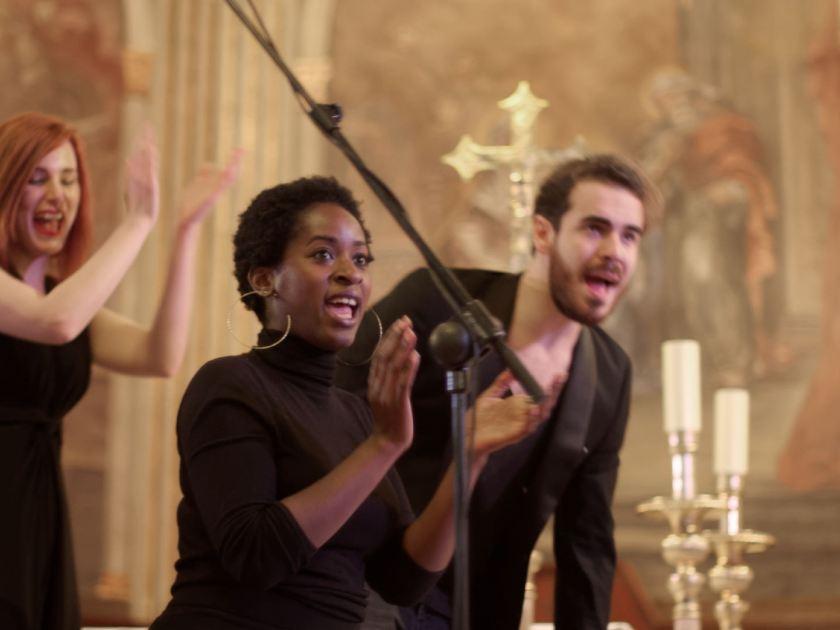 Cantante de gospel aplaudiendo. Concierto navideño del coro Gospel Factory en la Parroquia de Nuestra Señora de las Victorias de Madrid. Fotografía de Luis F. Roncero.
