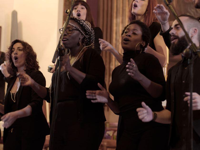 Coristas dando palmas. Concierto navideño del coro Gospel Factory en la Parroquia de Nuestra Señora de las Victorias de Madrid. Fotografía de Luis F. Roncero.