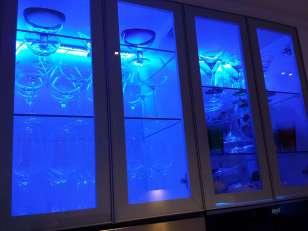 Cocina; Doble vitrina con puertas de cristal para lucir la cristalería e iluminada también por led azul.