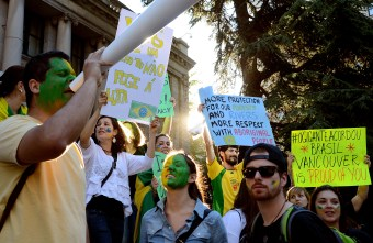 """Hundreds of Brazilians protest in front of the Vancouver Art Gallery in support of mass demonstrations by Brazilians all around the world, on June 24, 2013. With green and yellow painted faces, in reference to their native flag, they took the streets of Vancouver holding posters saying """"We don't need a World Cup, we need a better country"""" and """"Stop police brutality."""""""