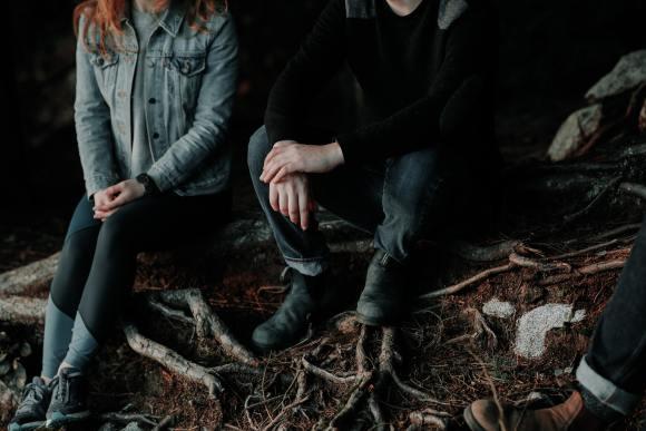 casal sentado lado a lado, com mãos separadas, provavelmente discutindo o fim do relacionamento.