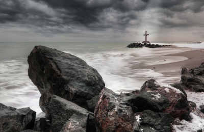 a cross by the ocean
