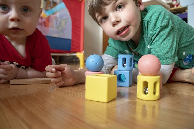 Boys building and playing with the geometric rattle trio set from Hape toys at https://lukeosaurusandme.co.uk