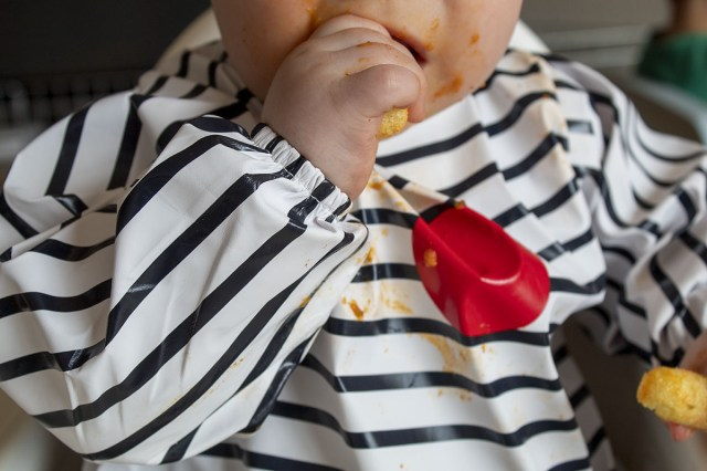 baby wearing a bib covered in food from weaning