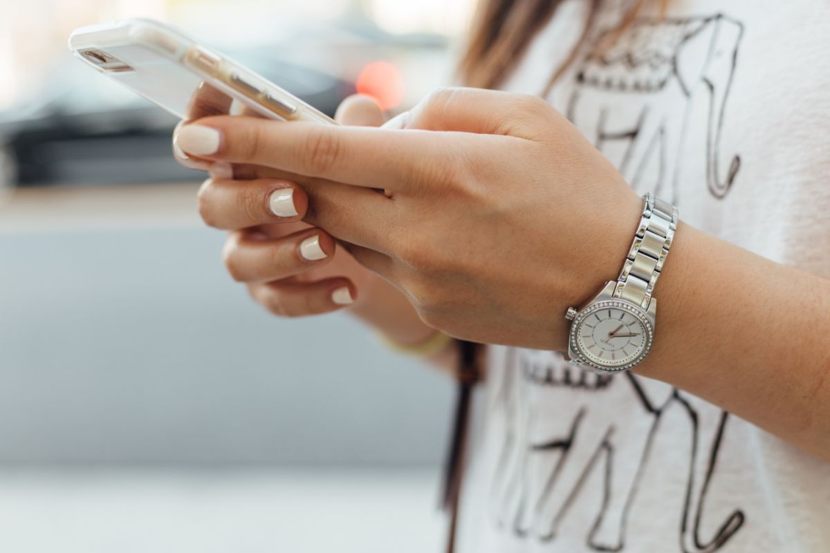 close up of a girl with pink nails looking at smart phone during the day time