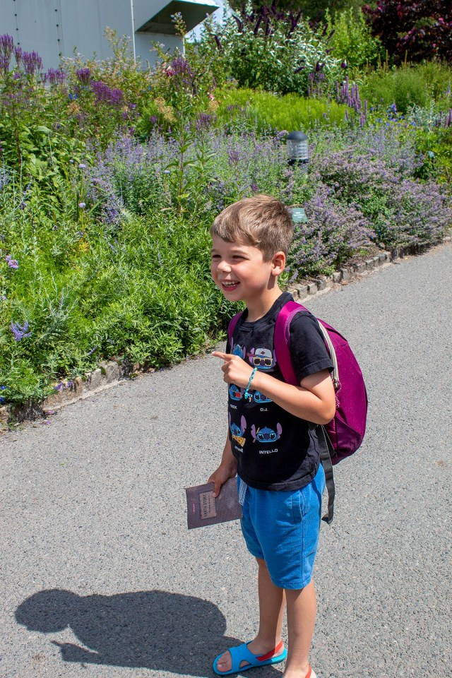 Luke smiling excitedly and pointing at some flowers in The Eden Project's outdoor gardens