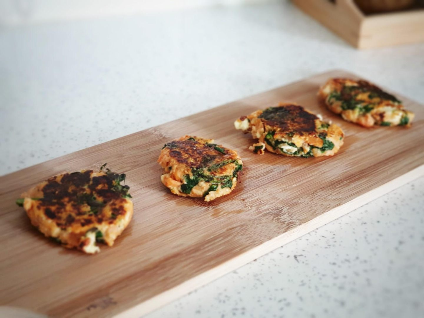 a collection of fritters on a wood chopping board