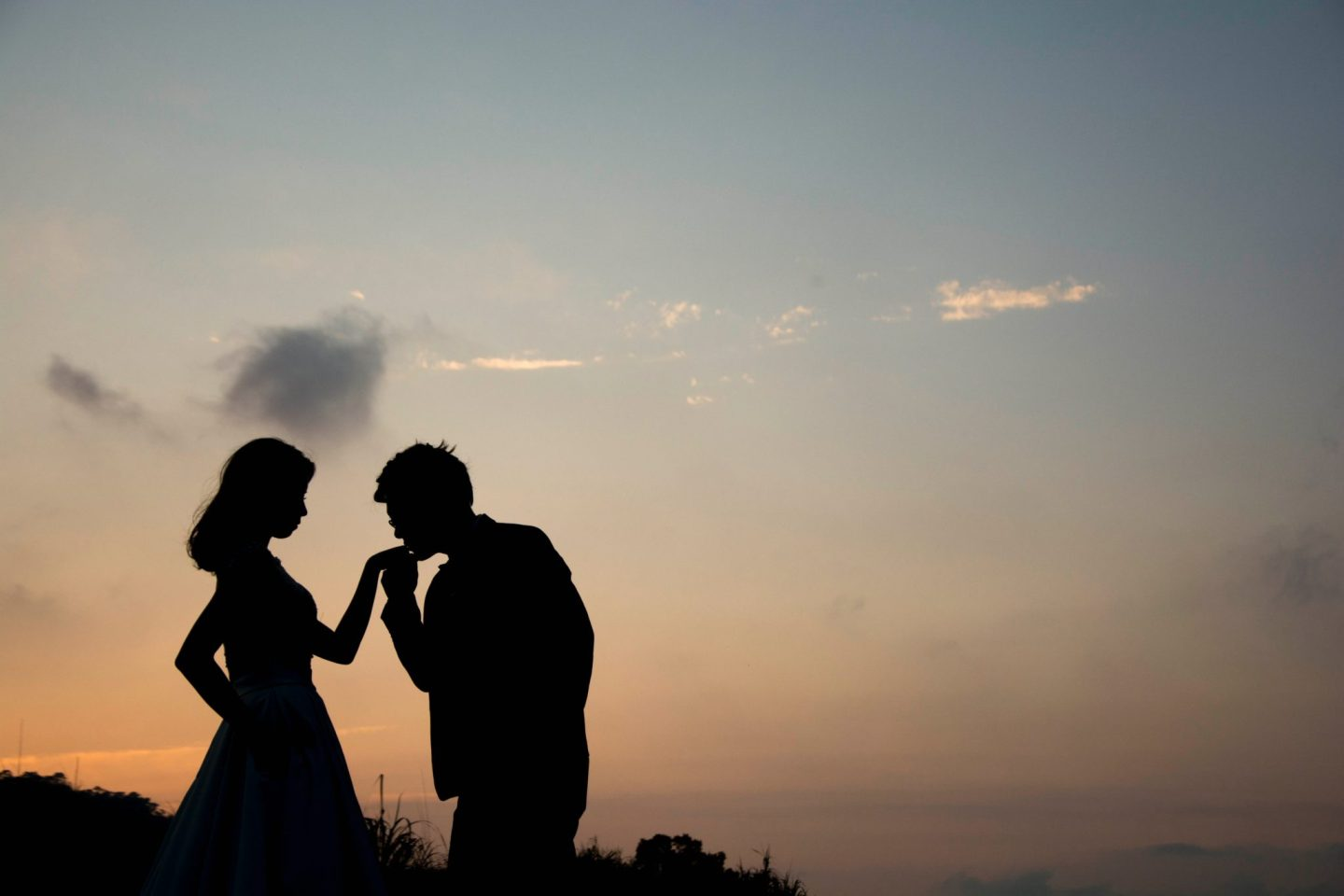 a silhouette of a man and a woman. The man is kissing them woman's hand.