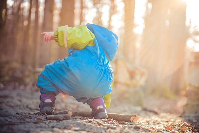 Toddler wearing a puddle suit kneeling down to pick up a twig in the woods.