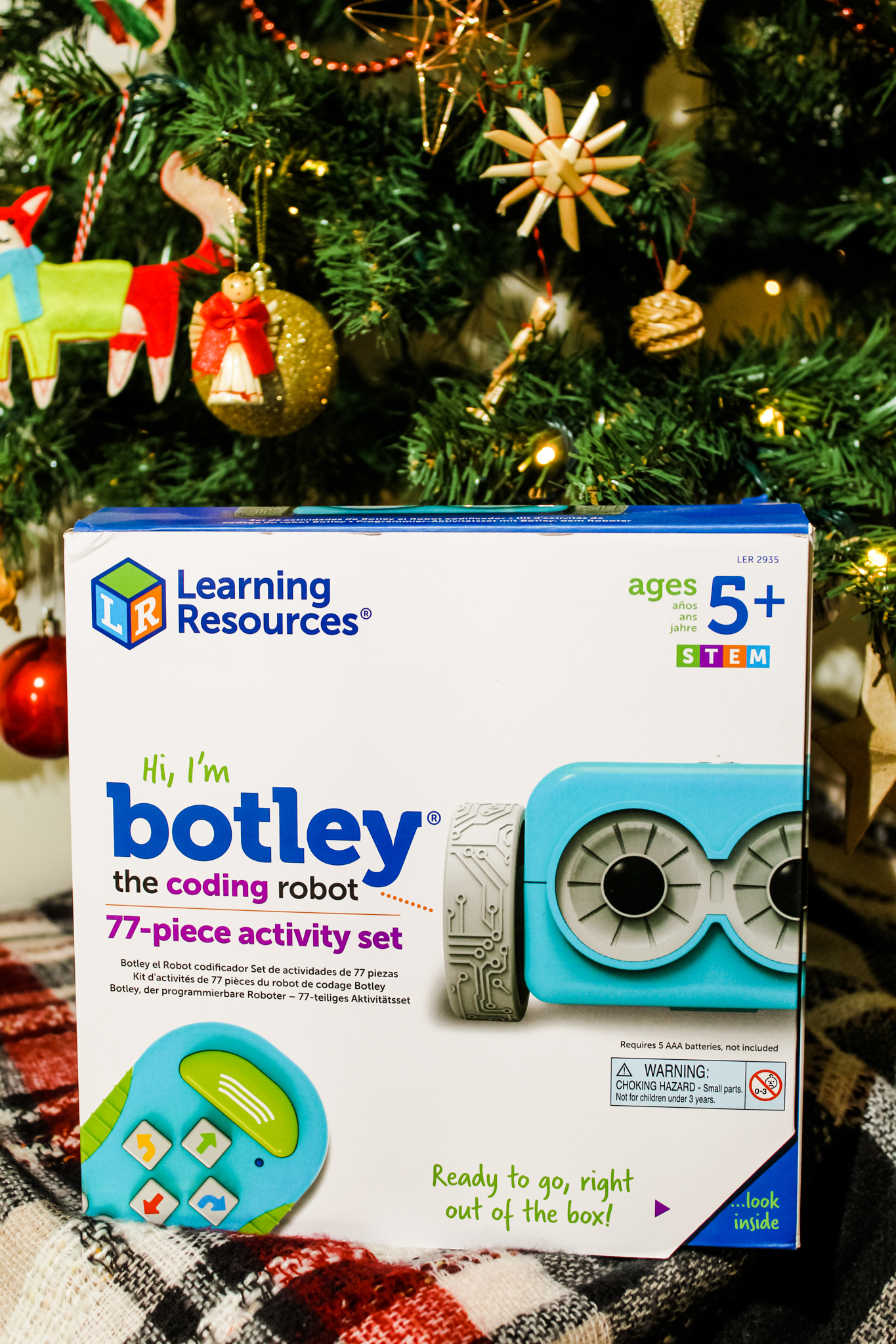 Botley The Coding Robot in front of a decorated Christmas tree.