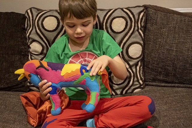 Boy playing with a customised multicoloured toy horse for a post about Petplan Equine Insurance
