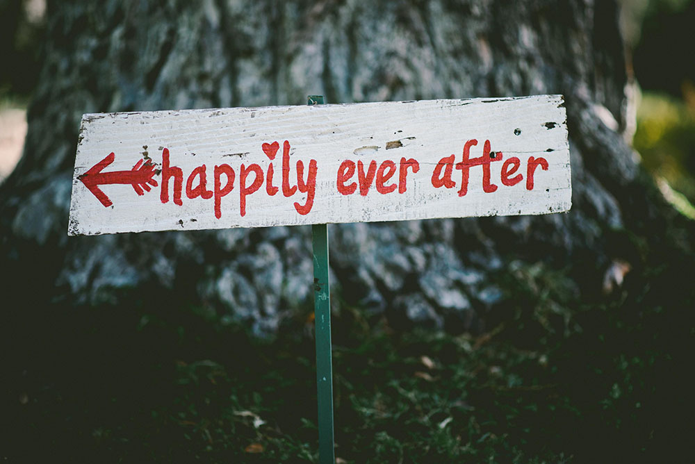White sign with happily ever after written on it in red paint