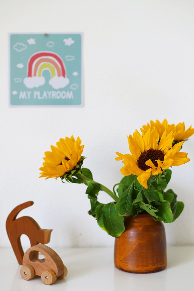 Sunflowers and some wooden toys with a poster in the background that says 'my playroom'