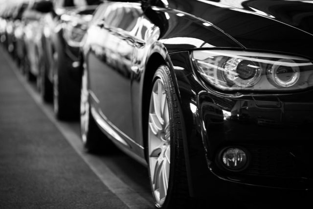 Black and white image of cars parked on the side of the road for a blog post about car loans.