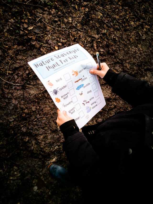 the nature scavenger hunt printable is being held up while a child looks at it. in the background is the forest floor