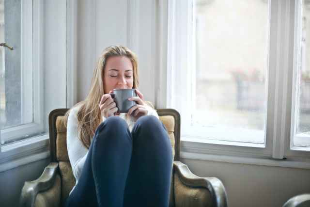 woman holding gray ceramic mug