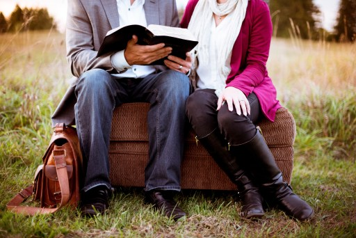 A couple sit together outside sharing their open bible