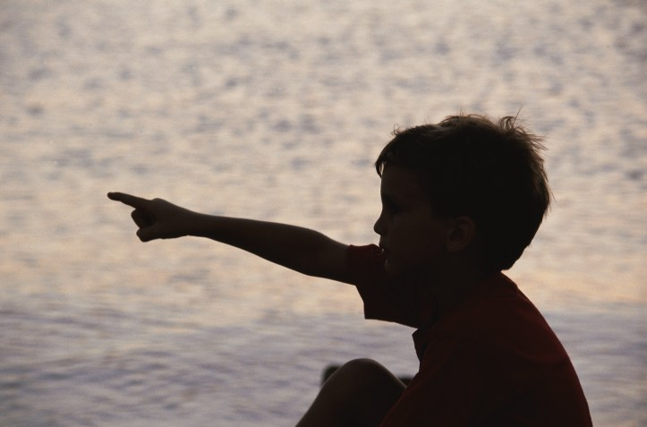 Silhouette of a young child pointing to the left