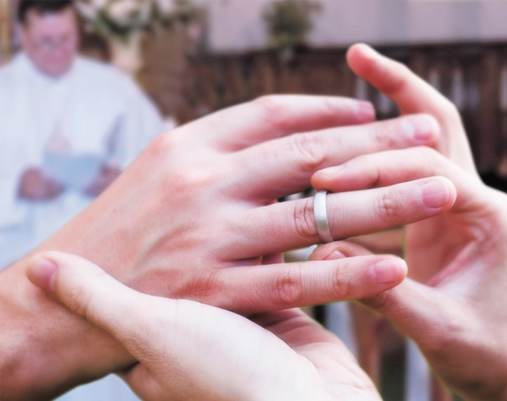 A close-up of one man's hands putting a wedding ring on another man's hands. A priest is out of focus in the background.