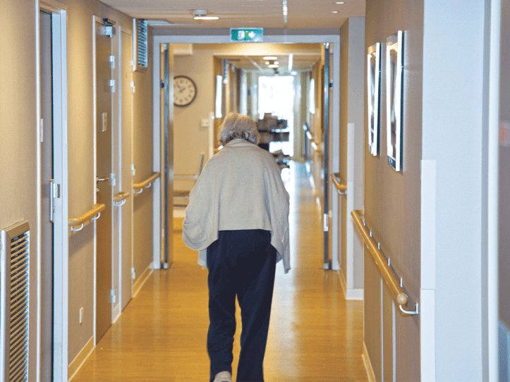 An elderly lady walking done the hallway of a residential care home.