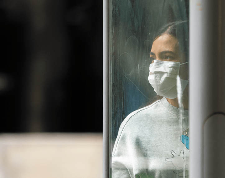 A young woman wearing a mask isgazing out through a window