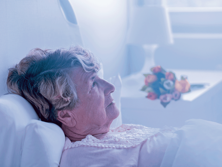 Aged woman laying in a bed thinking.
