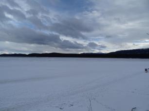 Ein Foto der Schwaene ohne Zoom. Zu sehen nichts als ein riesiger, zogefrorener See und ein paar Berge und Wolken im Hintergrund.