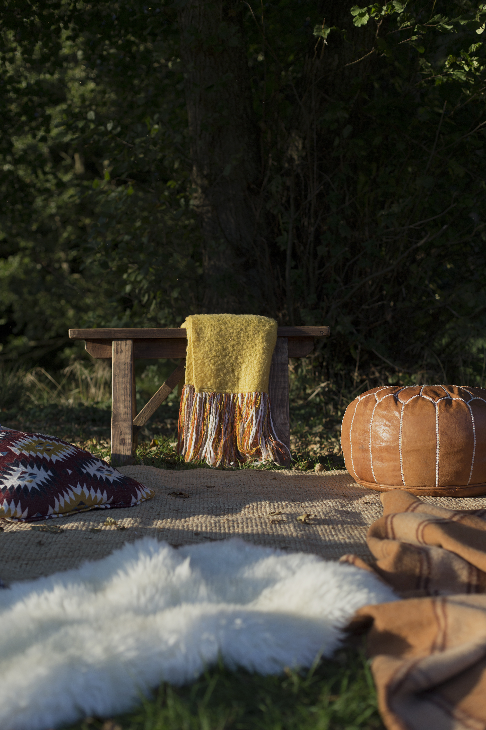 Outdoor rugs, morrocan pouffe, sheepskin and cushions under tree