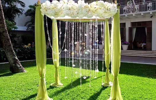 Свадебная арка из цветов и зеленой ткани