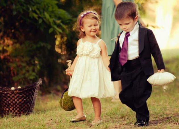 Мальчик и девочка идут за руки на свадьбе