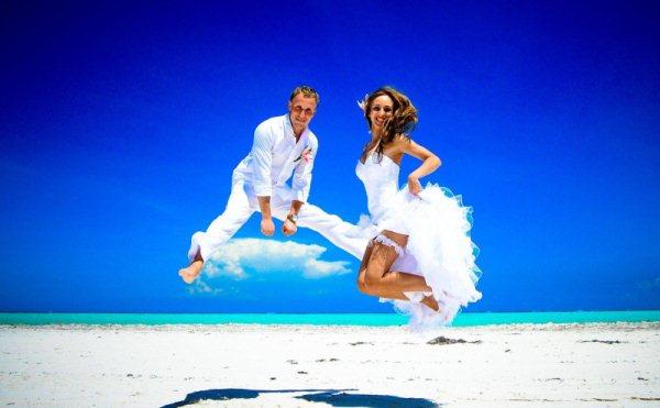 молодожены прыгают на песке