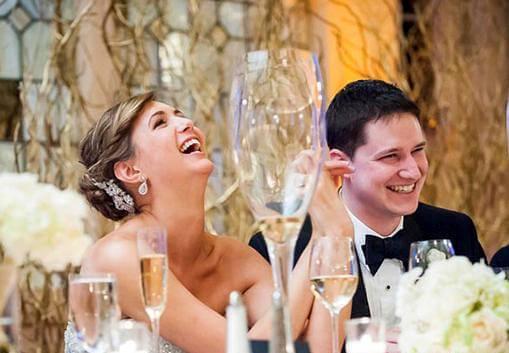 молодожены смеются за столом