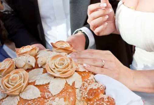 свадебный каравай отламывает невеста