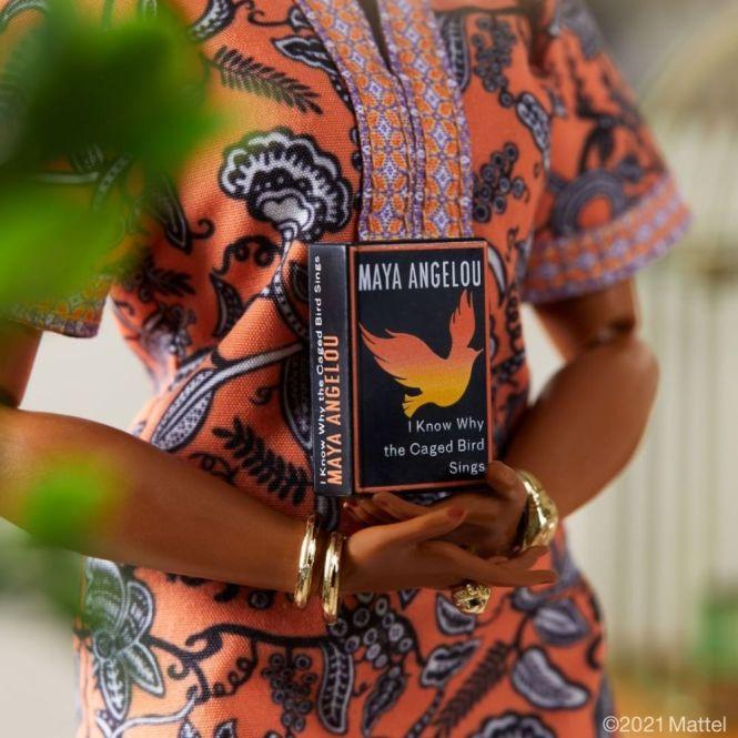 Barbie Maya Angelou: detalhe da capa do livro em miniatura que vem com a boneca, de capa preta com detalhes em cores quentes e título em branco.