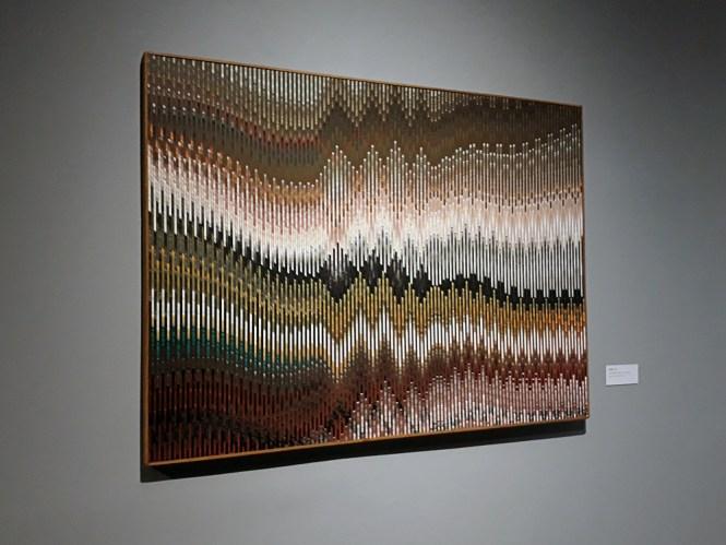 Quadro colorido, em diversas cores e tipos de tons, onde o uso de linhas de diferentes espessuras formando ondas e picos possibilitam efeitos de ilusão de ótica.