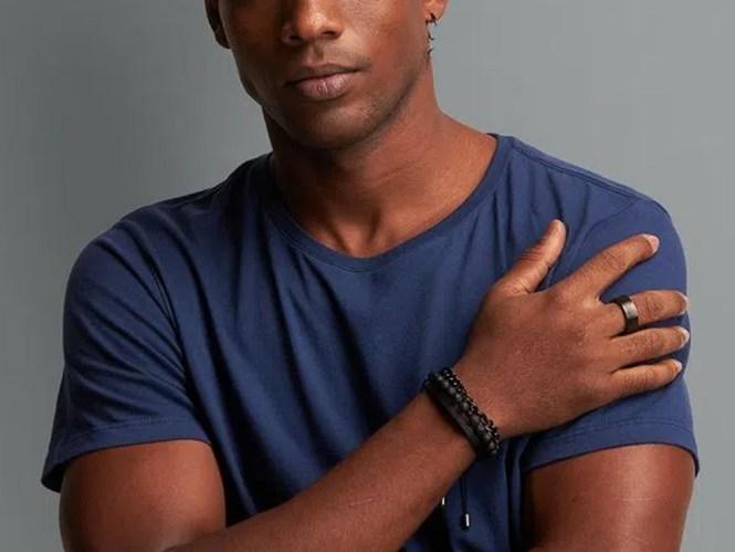 Foto de um homem negro, que mostra do nariz ao peito, usando uma camisa de gola careca azul. Sua mão direita está na frente do corpo, tocando o ombro esquerdo, e ele usa pulseiras artesanais.