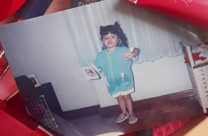 Foto de Luly Lage aos 3 anos, vestindo um macacão curto e marias-chiquinhas nos cabelos, segurando um estojo de maquiagem infantil na mão direita. Ao redor da foto, que é analógica, foram colocados itens de maquiagem já de adulta, todos em tons de rosa e vermelho, formando uma moldura.