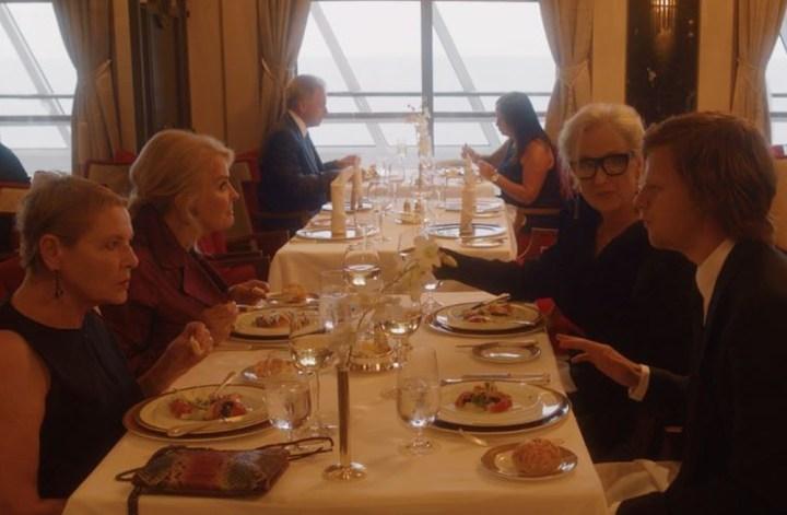 Cena do filme Let Them All Talk onde as personagens estão centadas à mesa em um restaurante bem iluminado, sendo elas Susan (Dianne Wiest) e Roberta (Candice Bergen) à esquerda e Alice (Meryl Streep) e Tyler (Lucas Hedges) de frente para elas, à direita. As três mulheres são idosas e têm cabelos brancos, enquanto o rapaz é um jovem de cabelos escuros.