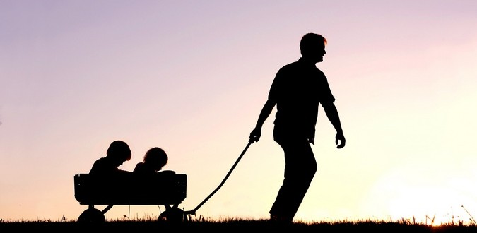 Silhouette of Father Pulling Sons in Wagon at Sunset