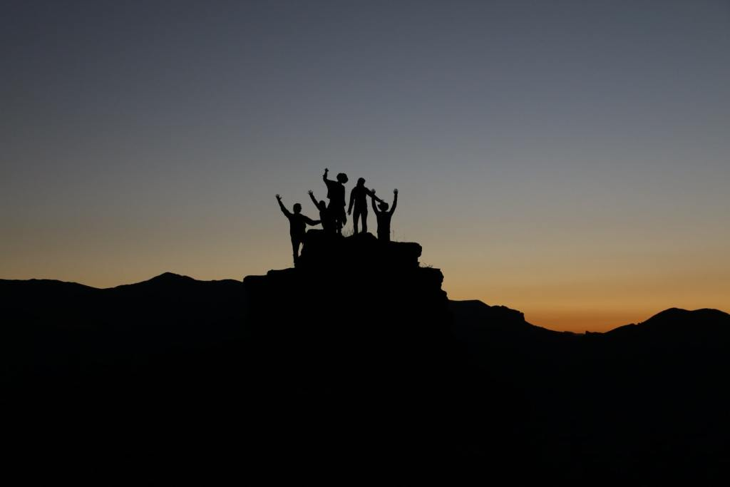 Group of adults standing on top of a rock together