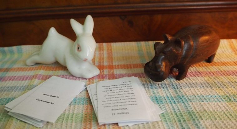 Bunny and hippo looking through manuscript