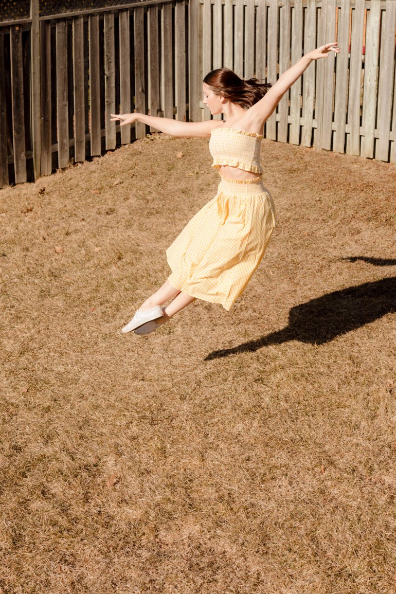 Emily Gilmore—Girl in yellow dress dancing in backyard