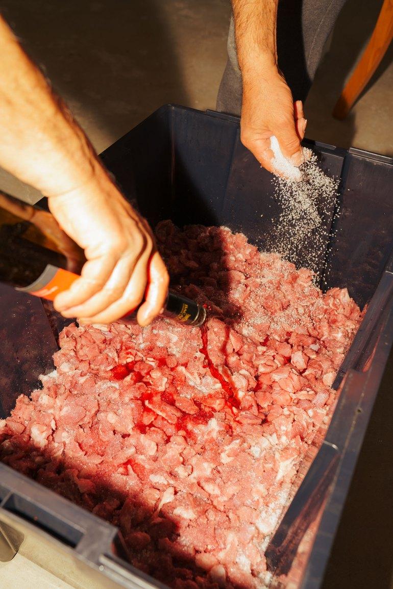 Portuguese chouriço seasoning the meat