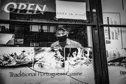restaurant owner in window in Toronto by George Pimentel