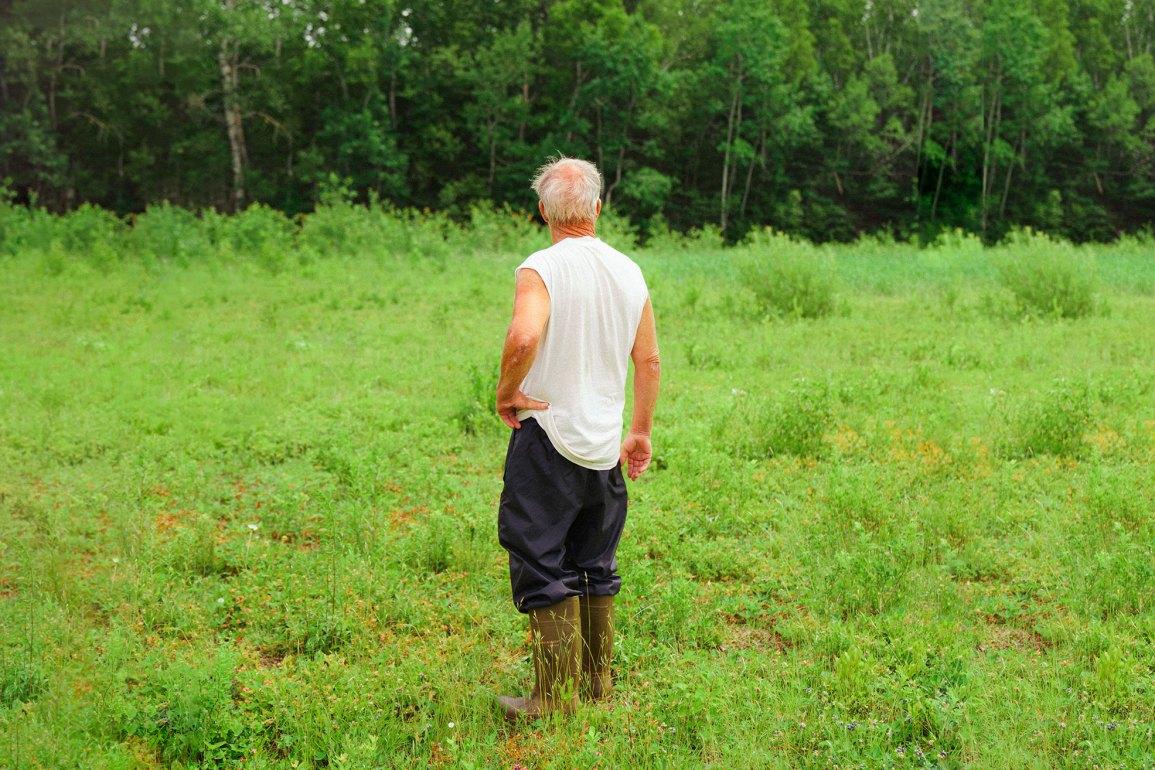 Portrait of man standing in grass. PEI