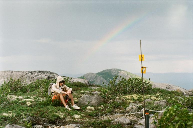 man and rainbow in Quebec mountains