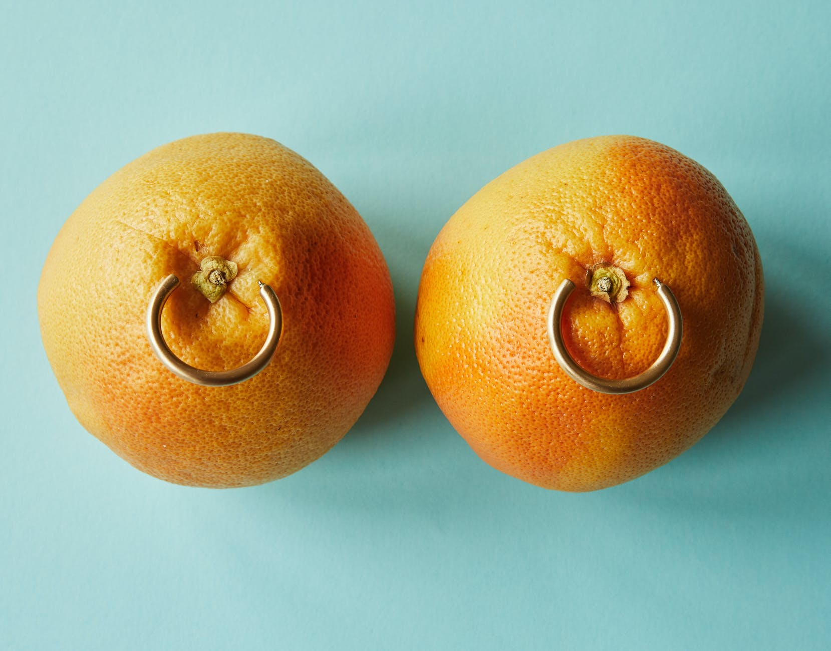 ripe tangerines with golden earrings against blue background