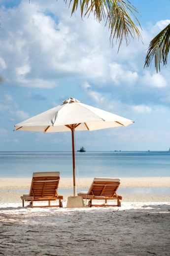 two brown wooden armchairs beside umbrella near seashore