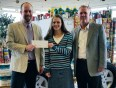 Matt Oquist with Motors Management, left, and GM John Hirsch present a donation to Suzanne Dewey with Family Pathways.